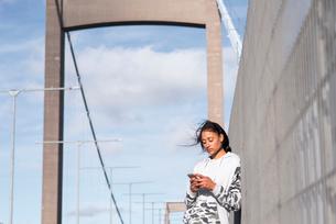 Sweden, Vastergotland, Gothenburg, Young woman listening music on smart phone on bridgeの写真素材 [FYI02206147]