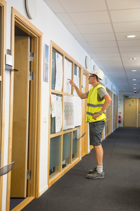 Sweden, Man wearing protective clothing standing in corridor and pointing on papers hung on wallの写真素材 [FYI02206150]