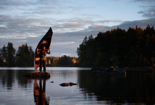 Sweden, Smaland, Mature man standing on rock in lake and holding boatの写真素材 [FYI02206153]