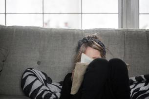 Sweden, Girl (4-5) reading book on sofaの写真素材 [FYI02206163]