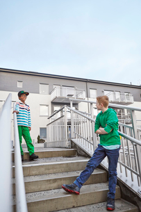 Sweden, Vastra Gotaland, Grimmered, Boys (8-9) standing on stairs and talkingの写真素材 [FYI02206195]