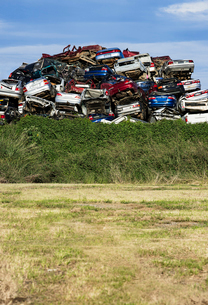 Australia, Queensland, Heap of scrapped cars over bushes and meadowの写真素材 [FYI02206205]