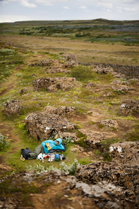 Iceland, Sudurland, Hiker lying in rocky wilderness and reading bookの写真素材 [FYI02206209]