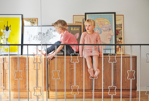Sweden, Girl and boy sitting on cupboard with pictures behind railingの写真素材 [FYI02206224]