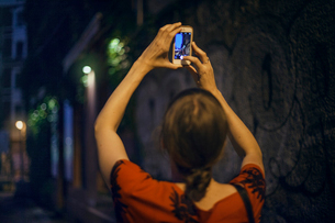 Germany, Berlin, Woman taking photo in city at nightの写真素材 [FYI02206246]