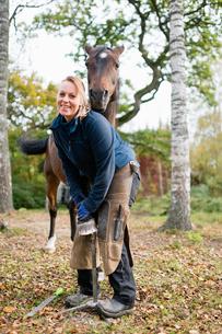 Sweden, Vastmanland, Bergslagen, Alvestorp, Smiling woman standing by horse in groveの写真素材 [FYI02206264]