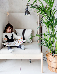 Sweden, Girl (4-5) sitting on bed and looking at pictures of butterflies in bookの写真素材 [FYI02206277]