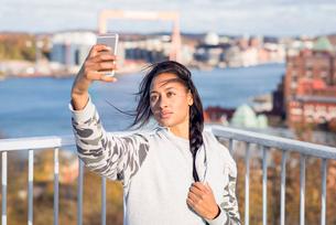 Sweden, Vastergotland, Gothenburg, Young woman taking selfie with smart phoneの写真素材 [FYI02206282]