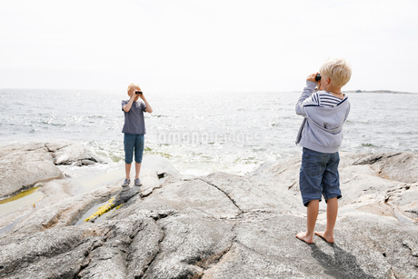Sweden, Stockholm Archipelago, Sodermanland, Orno, Two boys (6-7, 8-9) standing on rocky seashore anの写真素材 [FYI02206292]