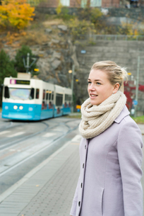 Sweden, Vastra Gotaland, Gothenburg, Young woman wearing overcoat with tram in backgroundの写真素材 [FYI02206315]