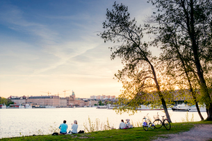 Sweden, Uppland, Stockholm, Djurgarden, People looking at city panorama across waterの写真素材 [FYI02206321]