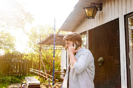 Sweden, Skane, Man using cell phone in back yardの写真素材 [FYI02206328]