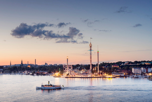 Sweden, Sodermanland, Stockholm, Illuminated Grona Lund amusement park at sunset seen across water wの写真素材 [FYI02206340]