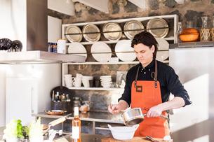 Sweden, Vastmanland, Man cooking dishの写真素材 [FYI02206341]