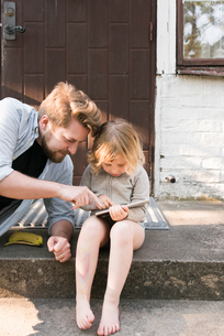 Sweden, Skane, Father and daughter (4-5) sitting on steps and using tabletの写真素材 [FYI02206347]