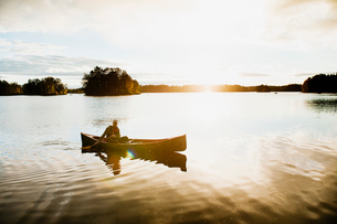 Sweden, Smaland, Mature man in boat on lake surrounded by forestの写真素材 [FYI02206372]