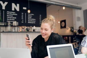 Sweden, Woman using mobile phone in cafeの写真素材 [FYI02206402]