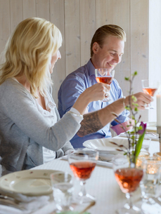 Sweden, Smiling man and woman raising wine glasses in celebratory toastの写真素材 [FYI02206443]