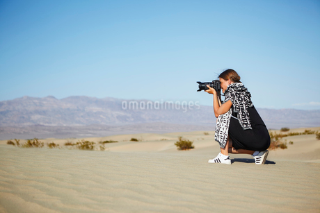 USA, California, Woman taking photographs in Death Valley National Parkの写真素材 [FYI02206463]