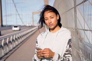 Sweden, Vastergotland, Gothenburg, Young woman listening music on smart phone on bridgeの写真素材 [FYI02206467]