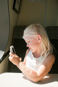 Sweden, Girl (6-7) using cell phone in ship cabinの写真素材 [FYI02206484]