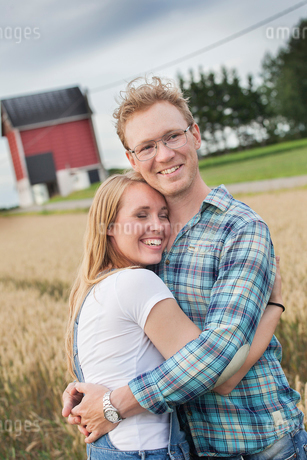 Finland, Uusimaa, Siuntio, Mid adult couple embracing in wheat fieldの写真素材 [FYI02206487]