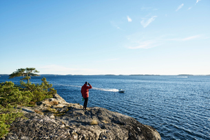 Sweden, Stockholm Archipelago, Varmdo, Bjorno, Man looking at view, motorboat in seaの写真素材 [FYI02206570]