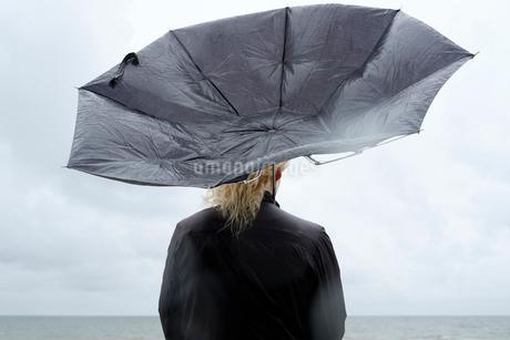 Poland, Niechorze, Woman under black umbrella watching Baltic Seaの写真素材 [FYI02206581]