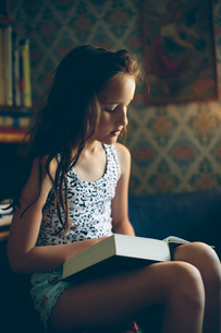 Sweden, Smaland, Mortfors, Portrait of reading girl (10-11)の写真素材 [FYI02206585]