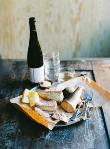 Sweden, Smoked fish, lemon, cutlery and bottle of wine on wooden tableの写真素材 [FYI02206615]