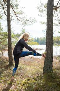 Sweden, Ostergotland, Lotorp, Woman stretching in forestの写真素材 [FYI02206621]