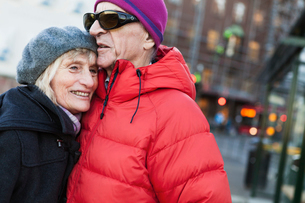 Sweden, Stockholm, Sodermalm, Senior couple hugging at bus stopの写真素材 [FYI02206629]