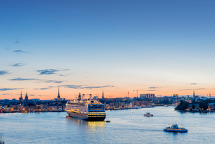 Sweden, Sodermanland, Stockholm, Illuminated city waterfront at sunset with ferry and ships passingの写真素材 [FYI02206635]
