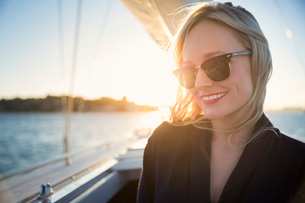 Australia, New South Wales, Sydney Harbor, Smiling woman in sunglasses on boat at sunsetの写真素材 [FYI02206643]