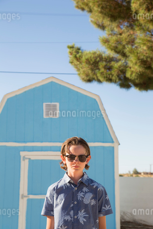 USA, California, Boy (14-15) wearing sunglasses standing in front of blue barnの写真素材 [FYI02206644]
