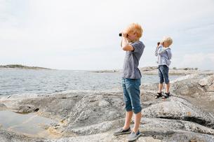 Sweden, Stockholm Archipelago, Sodermanland, Huvudskar, Two boys (6-7) (8-9) looking through binoculの写真素材 [FYI02206646]