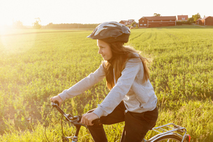 Sweden, Sodermanland, Girl (12-13) cycling against fieldの写真素材 [FYI02206660]