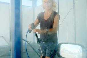 Sweden, Ostergotland, Skiren, Woman cleaning car in carwashの写真素材 [FYI02206690]