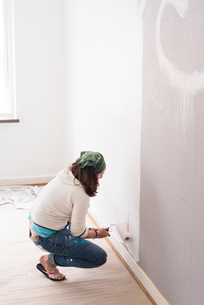 Sweden, Woman crouching in room and painting wallの写真素材 [FYI02206706]