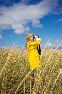 A young boy in wet weather gear looking through binocularsの写真素材 [FYI02206728]