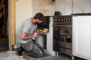 Sweden, Mature man repairing traditional oven in kitchenの写真素材 [FYI02206751]