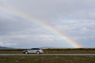 Sweden, Harjedalen, Rainbow over silver car on country roadの写真素材 [FYI02206773]