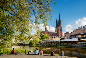 Sweden, Uppland, Uppsala, Fyris, People sitting on jetty by pondの写真素材 [FYI02206777]