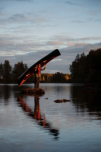 Sweden, Smaland, Mature man standing on rock in lake and holding boatの写真素材 [FYI02206784]