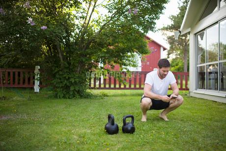 Sweden, Norrland, Vasterbotten, Mature man crouching next to weights on lawn in backyardの写真素材 [FYI02206799]