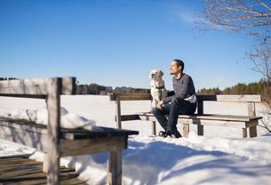 Sweden, Vasterbotten, Umea, Man sitting on bench with dog in winterの写真素材 [FYI02206810]