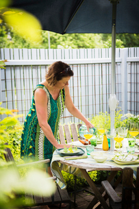 Sweden, Uppland, Woman setting table in gardenの写真素材 [FYI02206847]