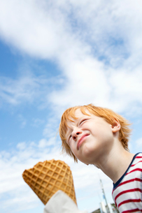 Sweden, Low angle view of redhead boy (6-7) eating ice cream against skyの写真素材 [FYI02206852]