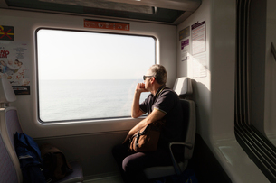 A man travelling on a train looking out the windowの写真素材 [FYI02206870]
