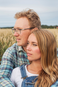 Finland, Uusimaa, Siuntio, Mid adult couple embracing in fieldの写真素材 [FYI02206923]